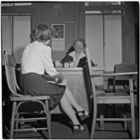 Mrs. Mallie Kerr sitting at her desk across from a teenage girl, Los Angeles, 1946