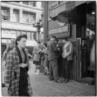 Woman and man talking to truant teenagers downtown, Los Angeles, March 1946