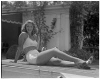 Actress Frances Staub poses poolside in a white bathing suit, Los Angeles, 1940s