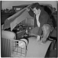 Manuel Sanchez looks at a truck engine during the War Assets Administration's surplus truck and trailer sale, Port Hueneme, May 1946