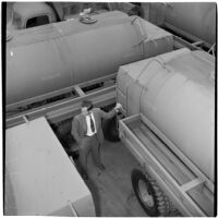 Man stands surrounded by gasoline trucks at the War Assets Administration's surplus truck and trailer sale, Port Hueneme, May 1946