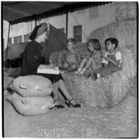 Mrs. Rosita Yacopi talks to three young children sitting on a hay bale at the Shrine Charity Circus, Los Angeles, June 1946