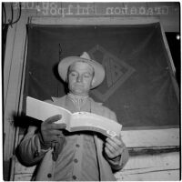 Graceton Philpot, head trainer for Louis B. Mayer stables, reading a booklet at Hollywood Park, Inglewood, 1946