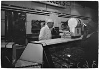 Butcher stands in front of a meat display case, Los Angeles, 1930s