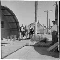 Four veterans at Port Hueneme for a Quonset hut and surplus military supply sale, Port Hueneme, July 15, 1946