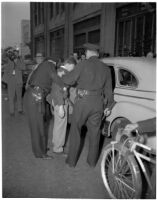 Police arresting Frank Bincia in front of Pacific Press, Inc. due to an altercation with John Sullivan, Los Angeles, August 6, 1946