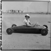 Al Pedrosa sitting in his soap box derby car on a barren stretch of road, Los Angeles, 1946
