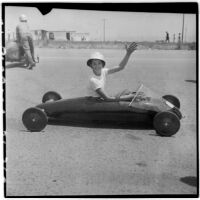 Al Pedrosa waving from his soap box derby car, Los Angeles, 1946