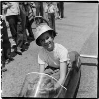 Al Pedrosa smiling in his soap box derby car while a crowd gathers for the race, Los Angeles, 1946
