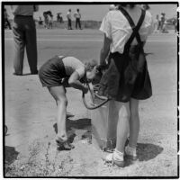 Two girls take a drink of water from a hose during a soap box derby race, Los Angeles, 1946