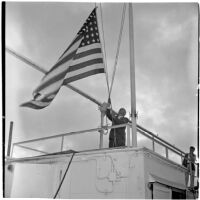 Tony Cornero raising the U.S. flag on his newly refurbished gambling ship, the Bunker Hill or Lux, Los Angeles, 1946