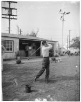 Blind veteran hitting a bucket of golf balls, Los Angeles, 1940s
