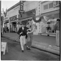 Fred Beck and L.B. Roquett walk arm-in-arm down the street during Anaheim's annual Halloween festival, Anaheim, October 31, 1946