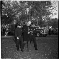 Anaheim Chamber of Commerce secretary-manager Ernest W. Moeller with two unidentified policemen on Halloween, Anaheim, October 31, 1946