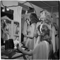 Charlotte Lander and two other models prepare for a fashion show in their dressing room, Los Angeles, September 1946