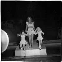 Woman and two little girls model swim suits in a fashion show that featured local designers, Los Angeles, September 1946
