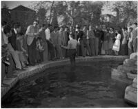 Man stands in a fountain on USC's campus while a crowd watches, Los Angeles, 1946