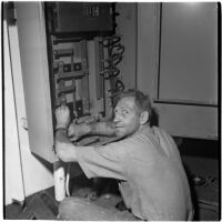 Man fixing a machine during the Army-Navy maneuvers that took place off the coast of Southern California in late 1946