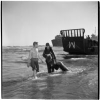 Two military officers wade through the water during the Army-Navy maneuvers that took place off the coast of Southern California in late 1946