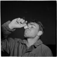 Sailor takes a swig of brandy from a tiny bottle during the Army-Navy maneuvers that took place off the coast of Southern California in late 1946