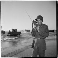 Captain David C. Morrison talking on his radio on the beach during the Army-Navy maneuvers that took place off the coast of Southern California in late 1946