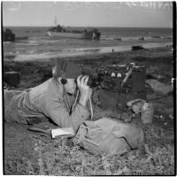 Soldier looking through binoculars during the Army-Navy maneuvers off the coast of Southern California in late 1946