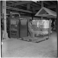 Employee pulls a cart of ceramic toilets at the Universal Vitreous China Factory, Mentone, circa 1948