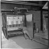 Employee loads newly made toilets into a kiln at the Universal Vitreous China Factory, Mentone, circa 1948
