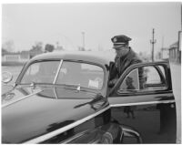 Police officer Dick Barlow writing a ticket for Dick Russell during a planned race to demonstrate the importance of following traffic laws, Los Angeles, 1947
