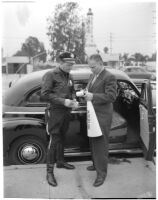 Dick Russell signing the speeding ticket he received from police officer Dick Barlow during a planned race to demonstrate the importance of following traffic laws, Los Angeles, 1947