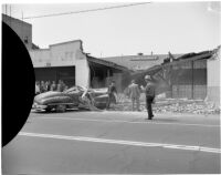 Crowd gathered to see the wreckage after an automobile swerved off the road and crashed into the front of a building, Los Angeles, 1940s