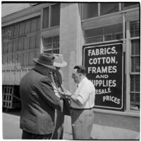 Three men talking outside of a warehouse or factory, California