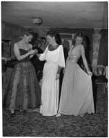 Three models in long dresses in their dressing room preparing for a fashion show, Los Angeles