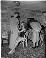 Models helping each other get ready in the dressing room before a fashion show, Los Angeles
