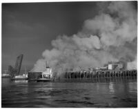 Smoke rises over L.A. Harbor while a coast guard boat battles the fire that began when the Markay oil tanker exploded, Los Angeles, 1947