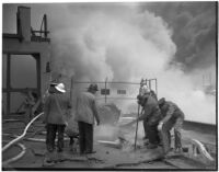 Fire fighters working to save a terminal in the L.A. Harbor which was threatened by flames when the Markay oil tanker exploded, Los Angeles, 1947