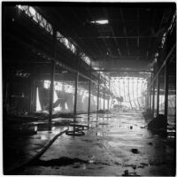 View from below of the damage done to a marine terminal after the Markay oil tanker exploded in L.A. Harbor, Los Angeles, 1947