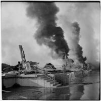 Smoke rises over the damage done to a marine terminal after the Markay oil tanker exploded in L.A. Harbor, Los Angeles, 1947