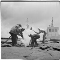 Fire fighters using an axe and a hose on a marine terminal in L.A. Harbor to fight at fire caused by the Markay oil tanker explosion, Los Angeles, 1947