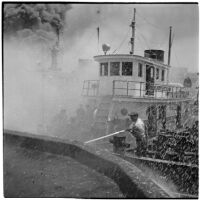 Man fighting fires from a Navy Tugboat after the Markay oil tanker explosion in L.A. Harbor, Los Angeles, 1947