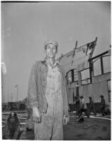 Man standing in front of the wreckage of Berth 153, a terminal in L.A. Harbor that was destroyed when the Markay oil tanker exploded, Los Angeles, 1947