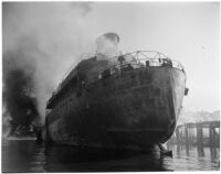 Ship amid smoke rising from the Markay oil tanker explosion in L.A. Harbor, Los Angeles, 1947