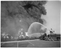 Fire fighters hose down one of many fires that raged after the Markay oil tanker exploded in L.A. Harbor, Los Angeles, 1947