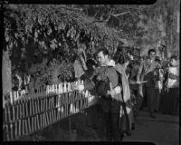 Spanish baritone Felipe Delgado lights candles while wearing a costume, Los Angeles, 1930s