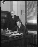 Officer Frank E. Walker provides his signature on a document with Deputy District Attorney Howard R. Hinshaw present, Los Angeles, 1930s