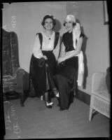 Mrs. Ray Callender and Mrs. Richard Illsley sit holding masks, Los Angeles, 1930s