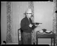 Dr. Ralph Wagner poses with guns and hat, Los Angeles, 1930s