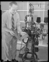 L.R. Bowles demonstrates a sock machine used at a rehabilitation plant for paroled workers, Los Angeles, 1930s