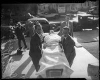 Choreographer and film director Busby Berkeley being carried into his manslaughter trial on a stretcher, Los Angeles, 1935