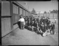 UCLA football coach William Spaulding reviews game strategy with team at Spaulding Field, Los Angeles, 1930s